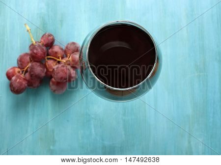Vibrant photo of glass of red wine with bunch of grapes, shot from above on turquoise blue wooden background texture, with copyspace. Selective focus on top of glass. Shallow depth of field