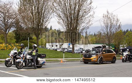 Vancouver, BC - April 20, 2015 - Gold movie car, fully loaded with camera and lighting equipment, escorted by Vancouver Motorcycle police, just coming out of the mobile movie set in the background. Bright, slightly overcast day.