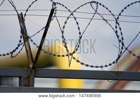 Barbed wire. It is used against people and stops attempts of penetration on the protected object.
