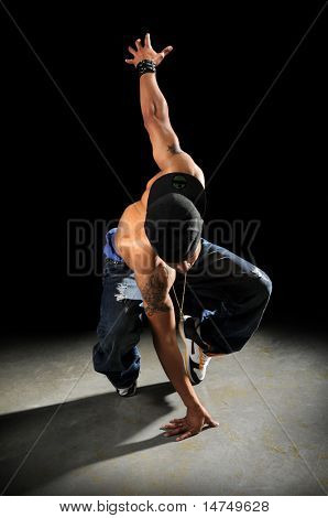 African American hip hop dancer performing over a dark background