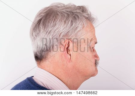 Portrait of a senior man wearing a small CIC (Completely in Canal) hearing aid