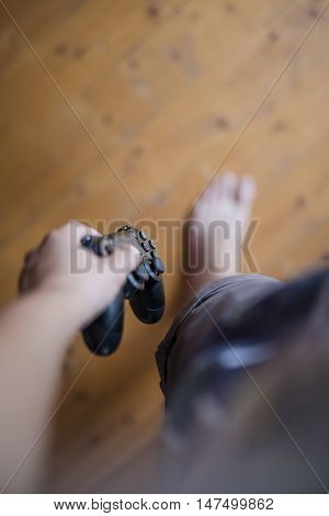 Gothenburg, Sweden - September 16, 2016: A shot from above of a young mans hand holding a video game controller for the Playstation 4, developed by Sony.