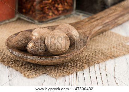 Nutmeg in a wooden spoon on old wooden table. Selective focus.