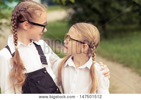Smiling young school children in a school uniform standing against a tree in the park at the day time. Concept of the girls are ready to go to school.