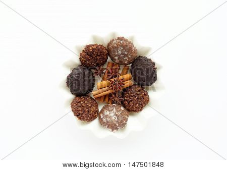 White porcelain plate with homemade german gingerbread ( Elisenlebkuchen) of three different varieties cinnamon sticks and star anise isolated on white background.