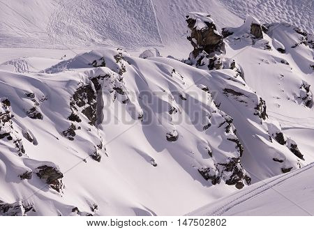 Freshly drifted untouched snow inbetween rock bands in the Swiss Alps.
