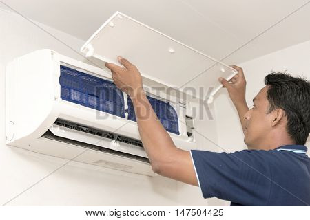 Portrait Young Man Adjusting Air Conditioning System