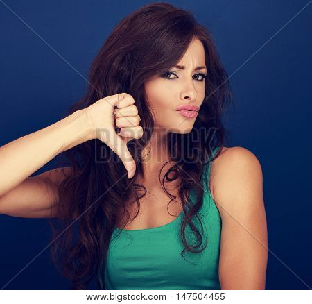 Beautiful Grimacing Woman With Long Curly Hair Showing Refuse Sign And Gesturing Thumb Down On Blue