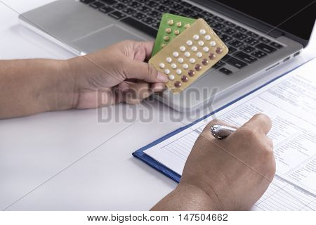 doctor hand holding birth control pills and pen over computer and patient history form on white table healthcare pharmacy and medicine concept