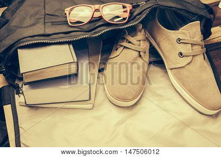 Top view of casual life style bag ; Old book,notebook,red glasses and casual shoes from inside bag.In Vintage tone