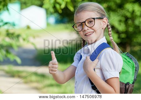 Smiling young school child in a school uniform standing against a tree in the park at the day time. Concept of the child are ready to go to school.