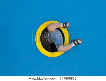 Funny kid playing in the playground. a child tries to climb through the ship's porthole.