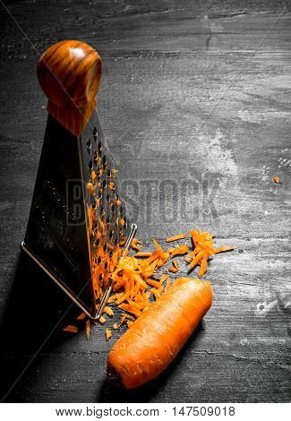 Grated carrots for the soup. On a black wooden background.
