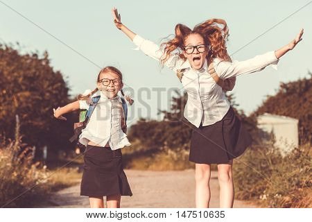 Smiling young school children in a school uniform jumping on the road in the park at the day time. Concept of the girls are ready to go to school.