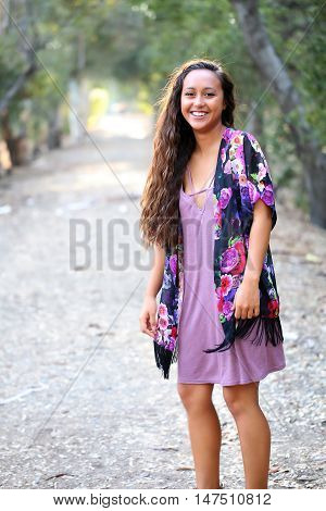 Happy, laughing young girl with long hair on a dirt path