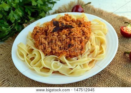 Pasta tagliatelle with meat sauce bolognese on a white plate. The traditional view of food.
