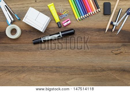 Workstation concept top view : pen,marker,pencil,rubber,sharpener,divider and color pencil on wooden background