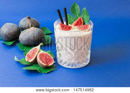 Glass of fig fruit smoothie fig slices straws and near scattered ripe fig fruits on the fig tree leaves on the blue background. Fig fruit smoothie glass. Horizontal. Daylight.