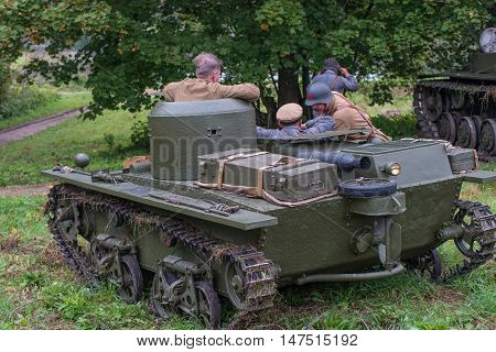 Gatchina, Russia - September 11, 2016: The historical reconstruction of World War II. Lightweight floating tank T-37A. The tank is in ambush, commanders are discussing a plan of action.