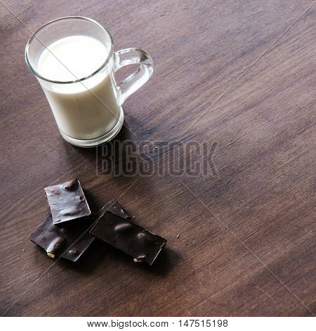 Bread with seeds, chocolate and cup of milk on the table.Top view. Eco life concept.