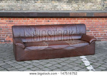 Dumped sofa in an abandoned industrial backyard
