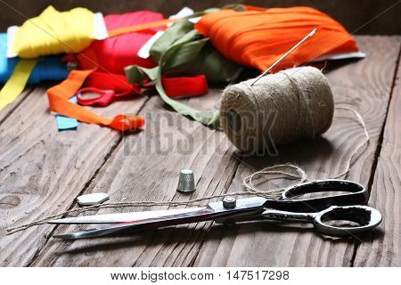 scissors and twine reel on the background of wooden boards
