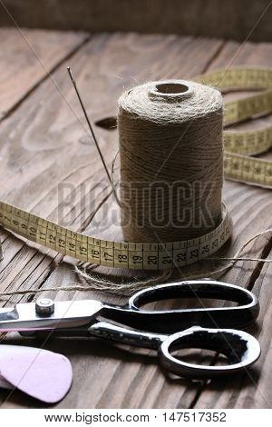 Scissors and spool of string close up on a background of wooden boards