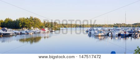 sailing and motorboats reflected in a lake and moored in a pier surrounded of trees