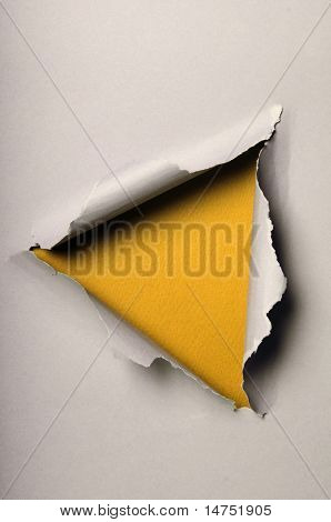 Old ripped paper forming triangle over yellow background