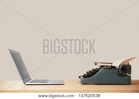 Old typewriter and laptop on table. Concept of technology progress