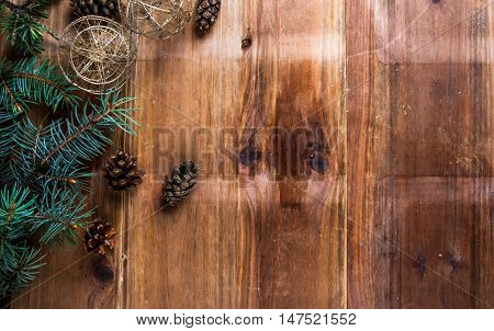 Christmas wooden background with branches of a Christmas tree, Christmas balls and cones, copy space