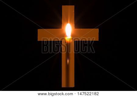Candle is glowing behind a hole in shape of Christian cross. Concept of Christianity