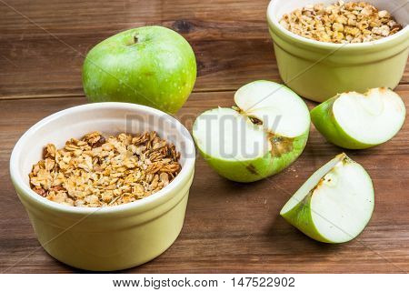 Freshly made autumn apple crumble with fresh green apples on a wooden table, top view