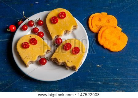 Funny food for a child for Halloween: the sandwiches in the shape of ghosts and slices of fresh pumpkin, carved cookie cutters in the form of a pumpkin