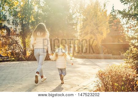 Family walk. Mother and daughter running through the park to the setting sun. Autumn Park.