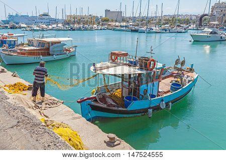 Heraklion, Greece - August 3, 2012: Fishermen Working With Old Nets Near Fishing Boats