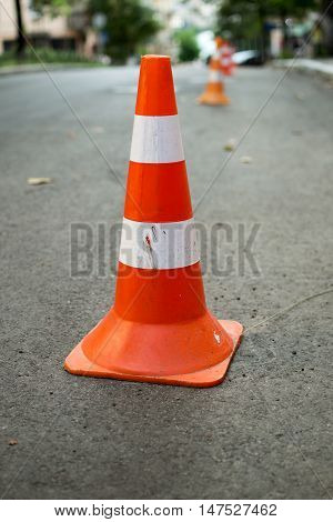 The orange and white cone on the road