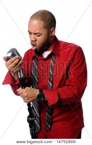 Portrait of African American man singing into vintage microphone