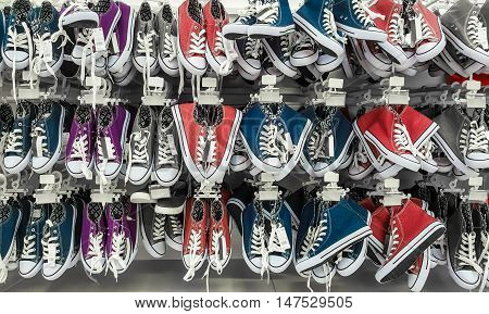 Many pair of sneakers in a store. Gym shoes.