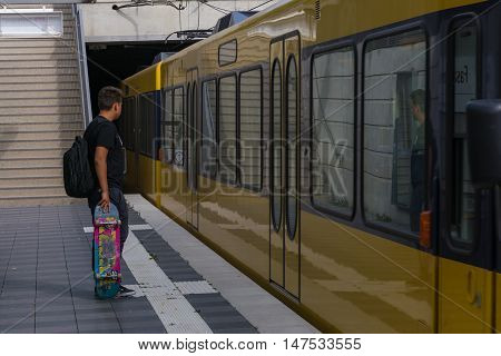 Teen Skateboard Waiting Holding Standing Train Subway Reflection