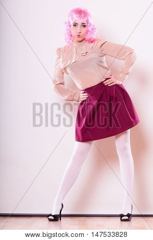 Portrait woman with pink wig creative visage makeup posing on gray background
