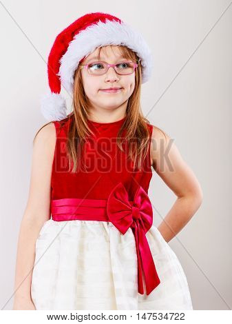 Christmas family time concept. Little girl looking like santas elf. Beautiful young lady wearing santa claus hat with white pompon. Small woman has red dress with bow and wears glasses.