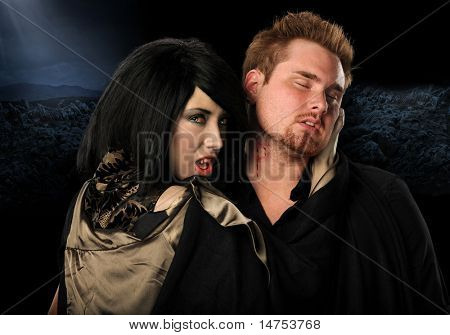 Vampire woman biting man on the neck