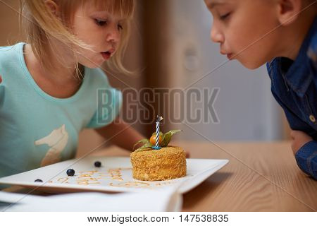 Birthday party in family. Girl blowing candles for her three years old
