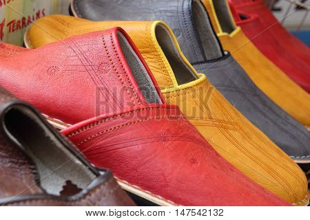 Row of colorful retro handmade mens slippers in red and yellow ochre