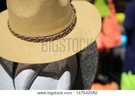 Straw fedora hats for men in beige and gray with blurred background