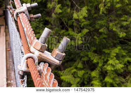 Two bolts connected to metall rope on suspention bridge