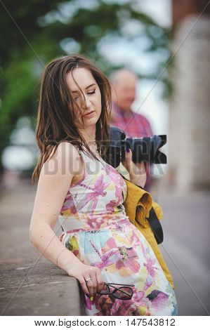 Outdoor summer smiling lifestyle portrait of pretty young woman having fun in the city in Europe in evening with camera travel photo of photographer