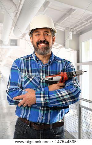 Senior Hispanic contractor inside building