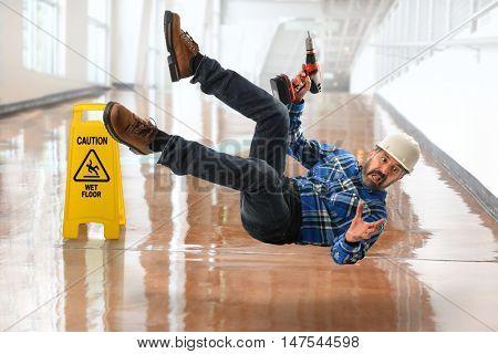 Senior Hispanic worker falling on wet floor
